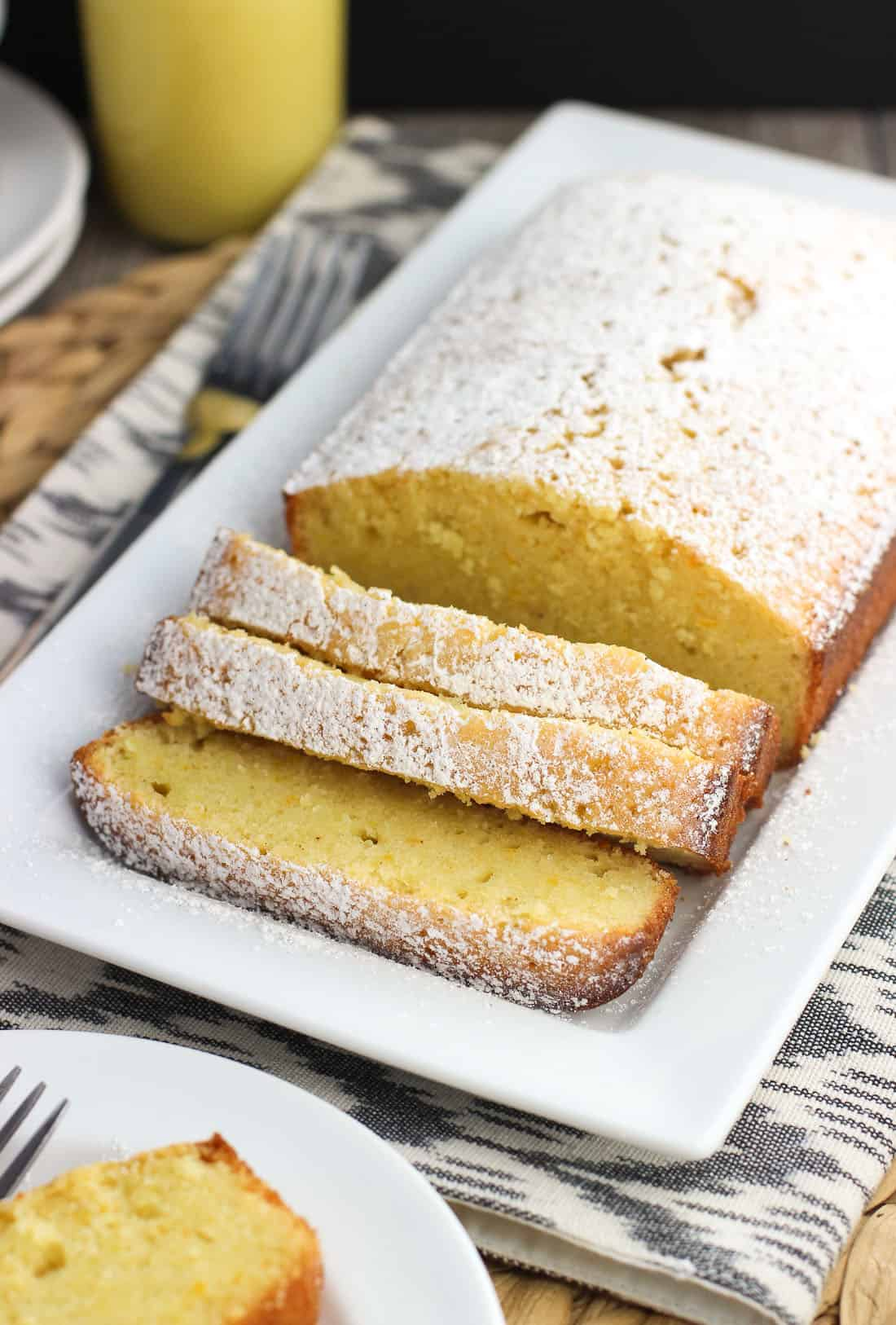 A loaf of pound cake on a tray, dusted with confectioners' sugar and cut into three slices