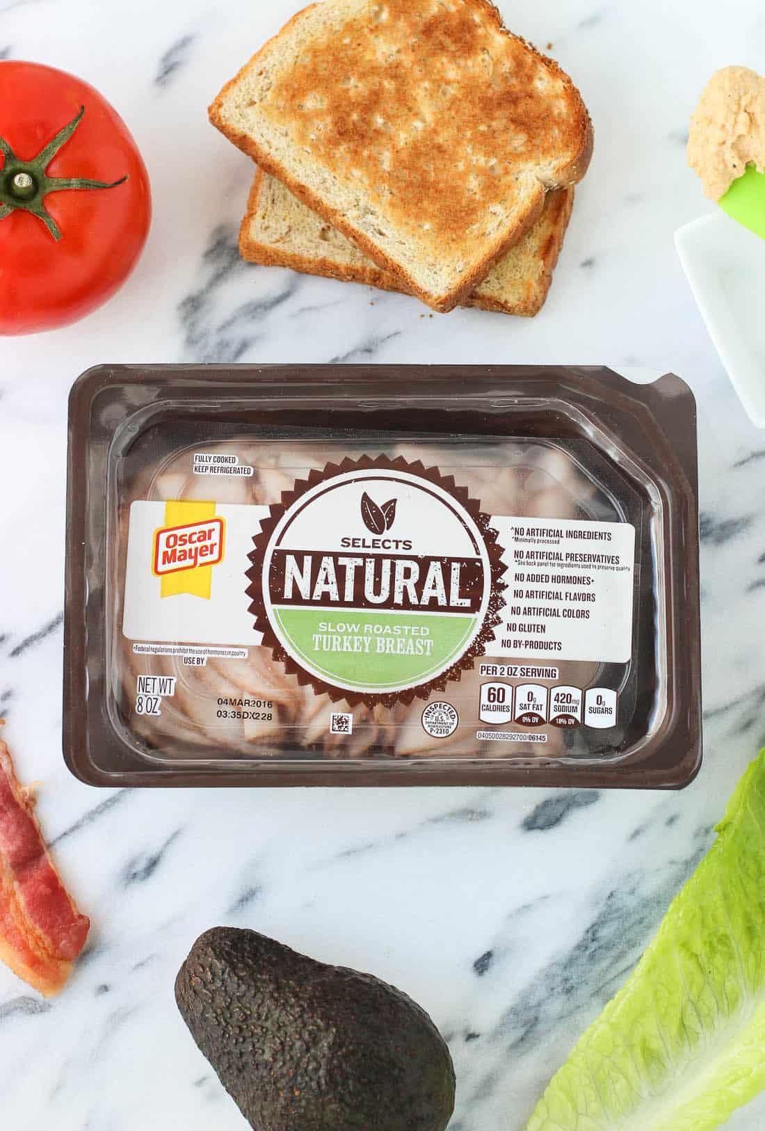 This hummus avocado turkey club sandwich features juicy tomato, bacon, turkey, mashed avocado, and creamy hummus, all on multigrain bread.