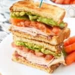 This hummus avocado turkey club sandwich features juicy tomato, bacon, turkey, mashed avocado, and creamy hummus, all on multigrain bread.