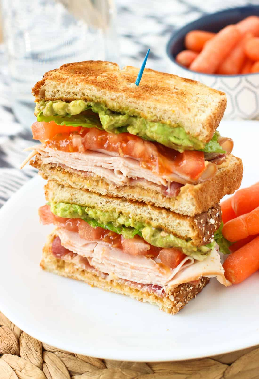 Two halves of the sandwich stacked on top of one another on a plate with baby carrots.