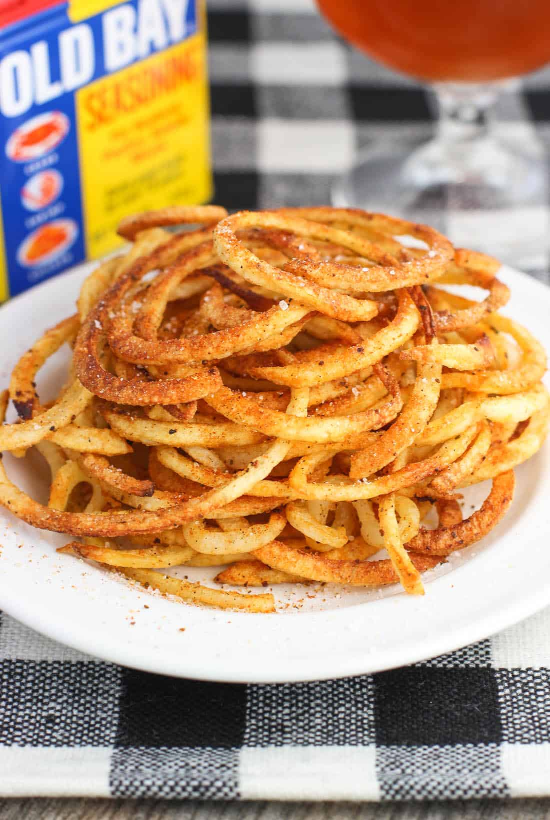 A heap of Old Bay seasoned curly fries on a plate.