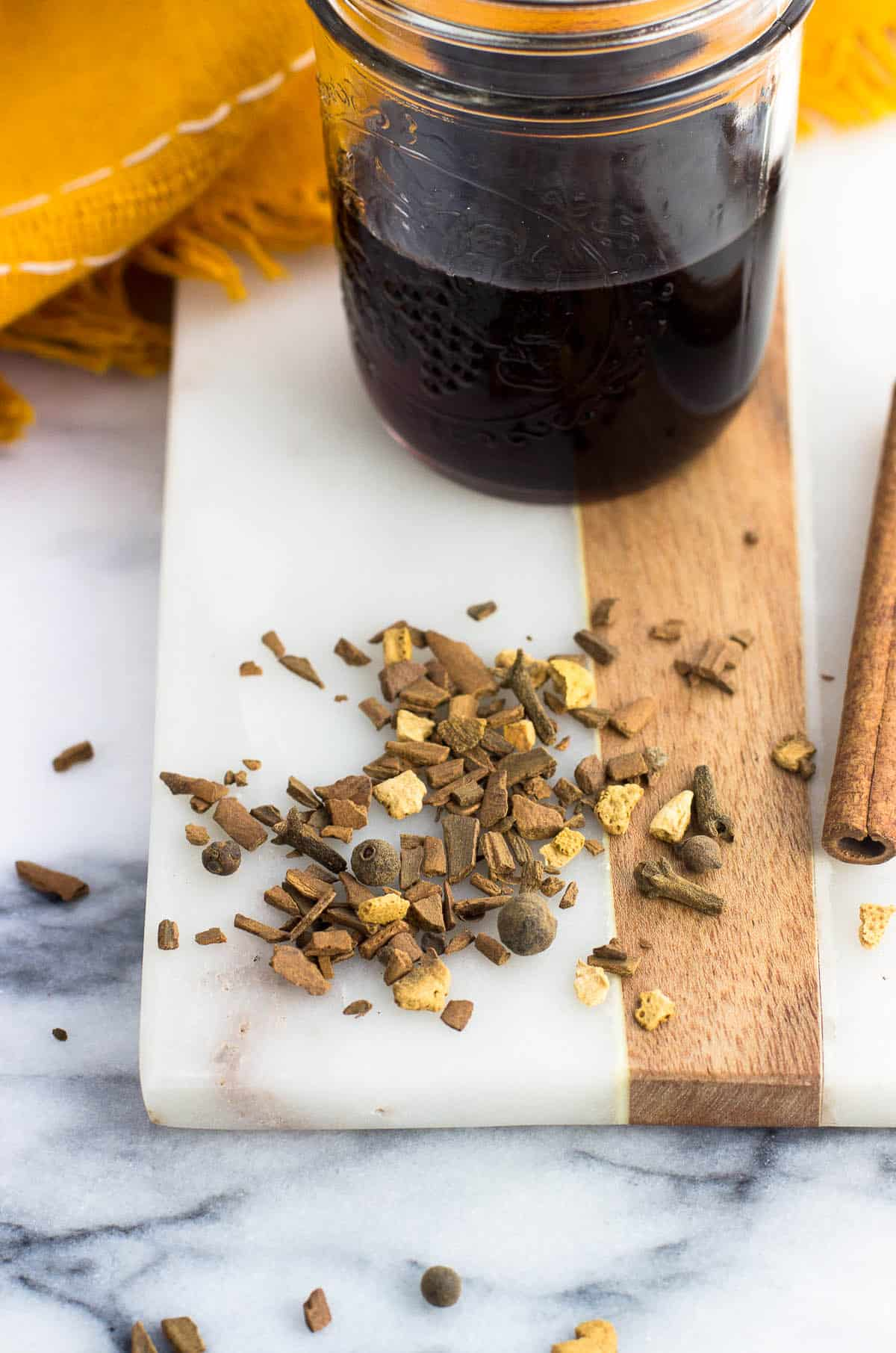 Dried mulling spices scattered on a marble board next to whole cinnamon sticks and a glass jar of wine