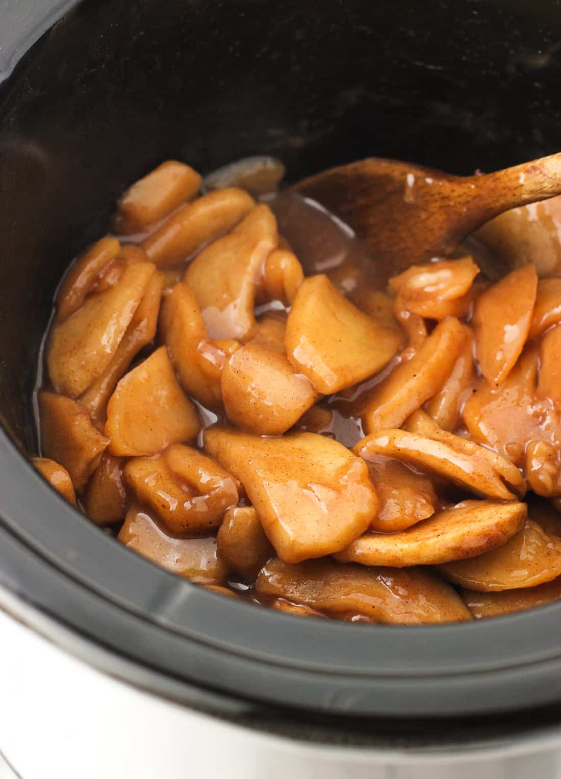 Stewed apple slices in a slow cooker with a wooden spoon.