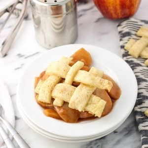 A serving of slow cooker apples on a dessert plate with a lattice pie topping.