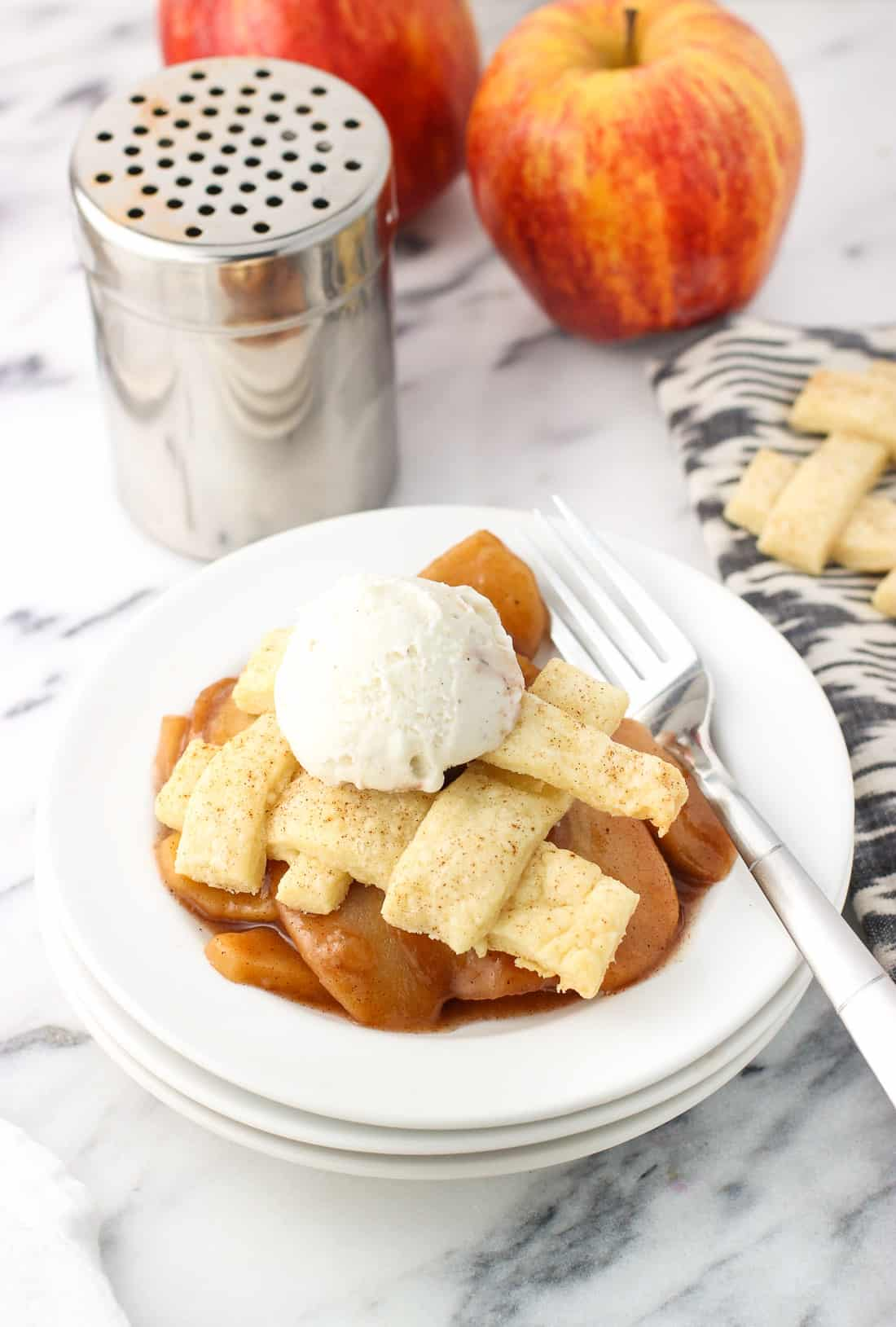 A slow cooker apple pie serving on a dessert plate with a fork and a small scoop of vanilla ice cream.