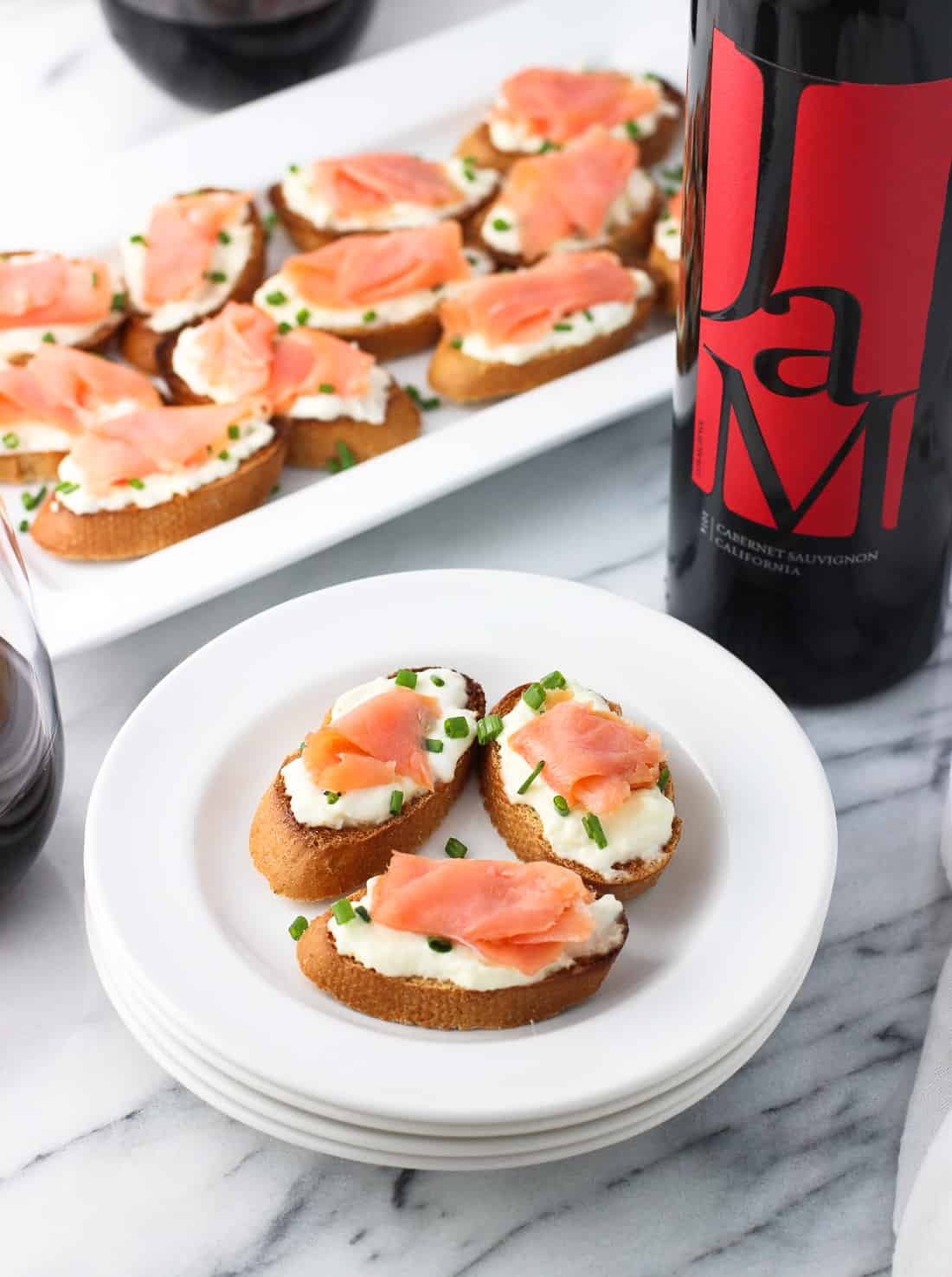 Crostini topped with burrata and a slice of smoked salmon on a plate next to a bottle of wine and the tray.