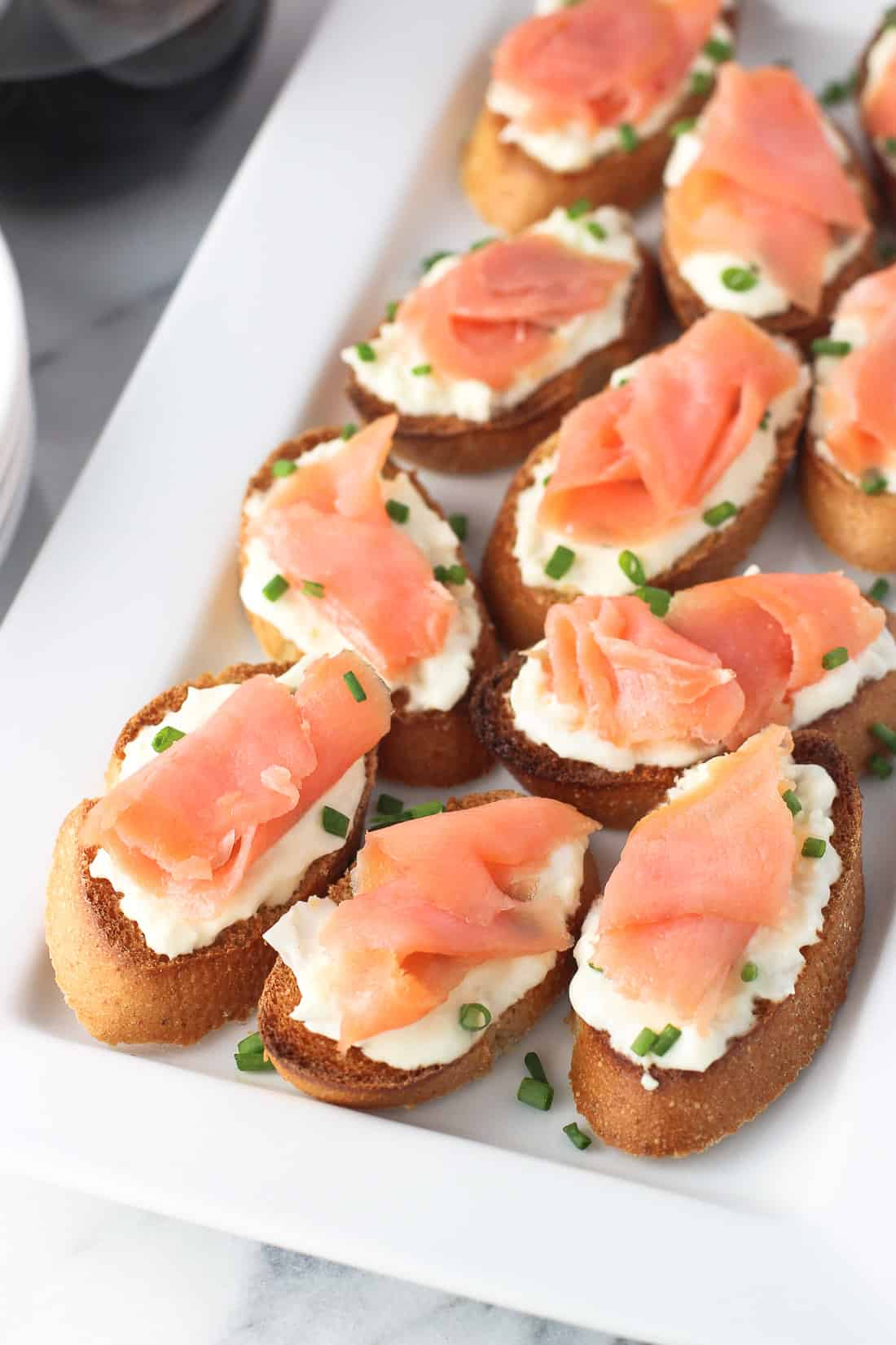 Crostini topped with burrata and a slice of smoked salmon on a tray.