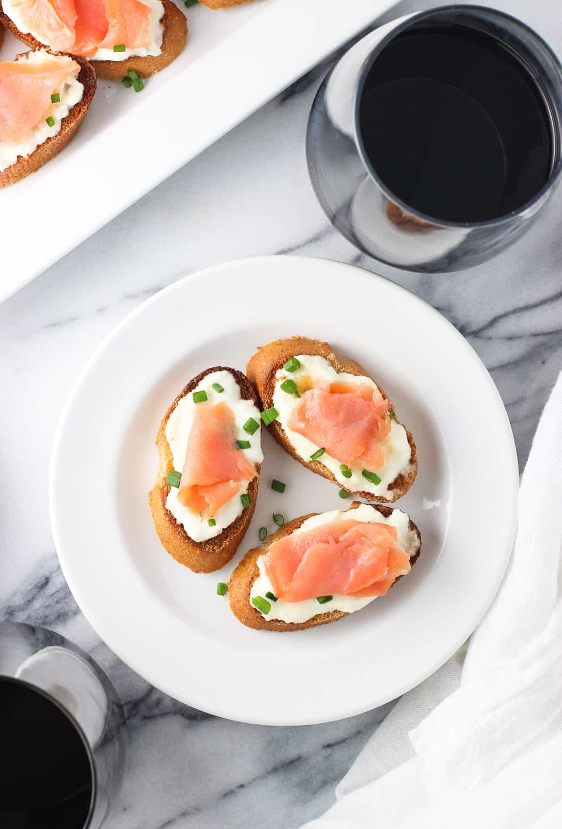 Three crostini on a plate next to a glass of wine and the crostini tray.