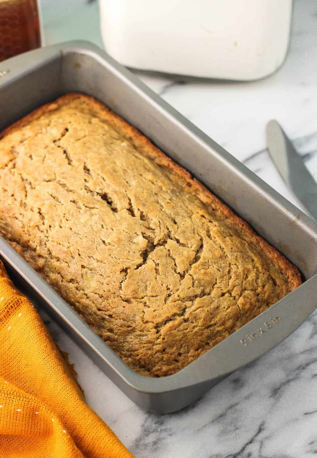 A loaf of baked banana bread in the tin.