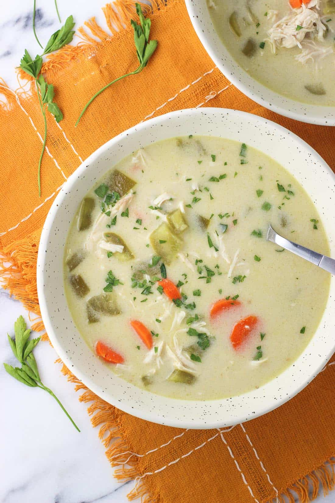 A bowl of coconut curry chicken soup with a spoon in it.