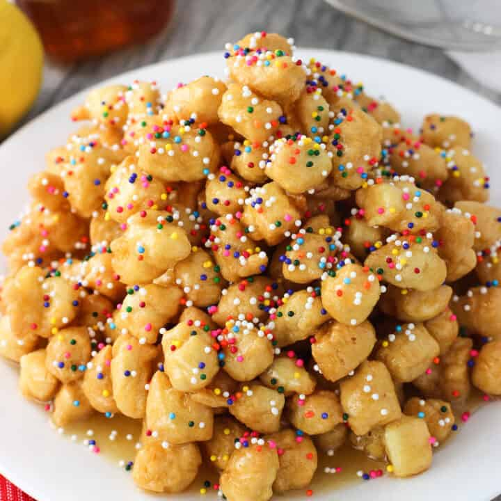 Struffoli on a plate covered in honey and rainbow nonpareils