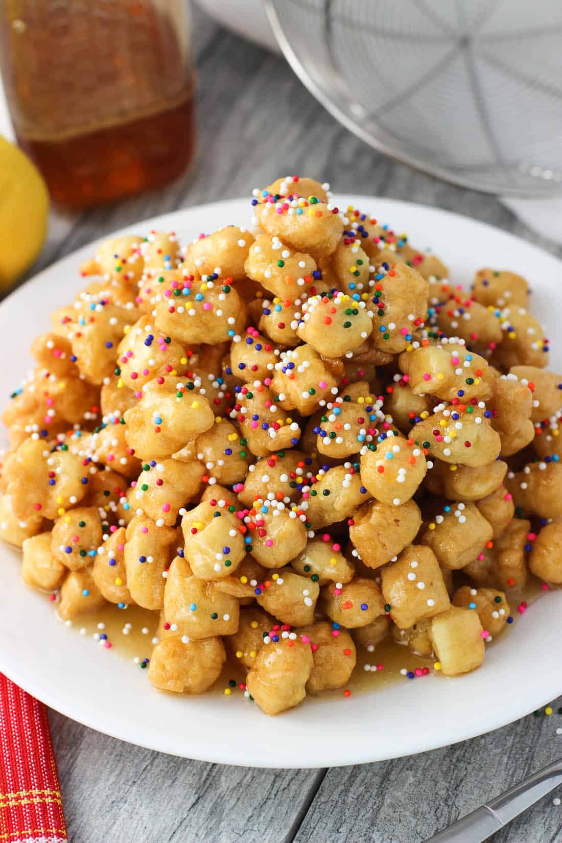 A pile of honey balls on a plate, covered in honey and nonpareil sprinkles