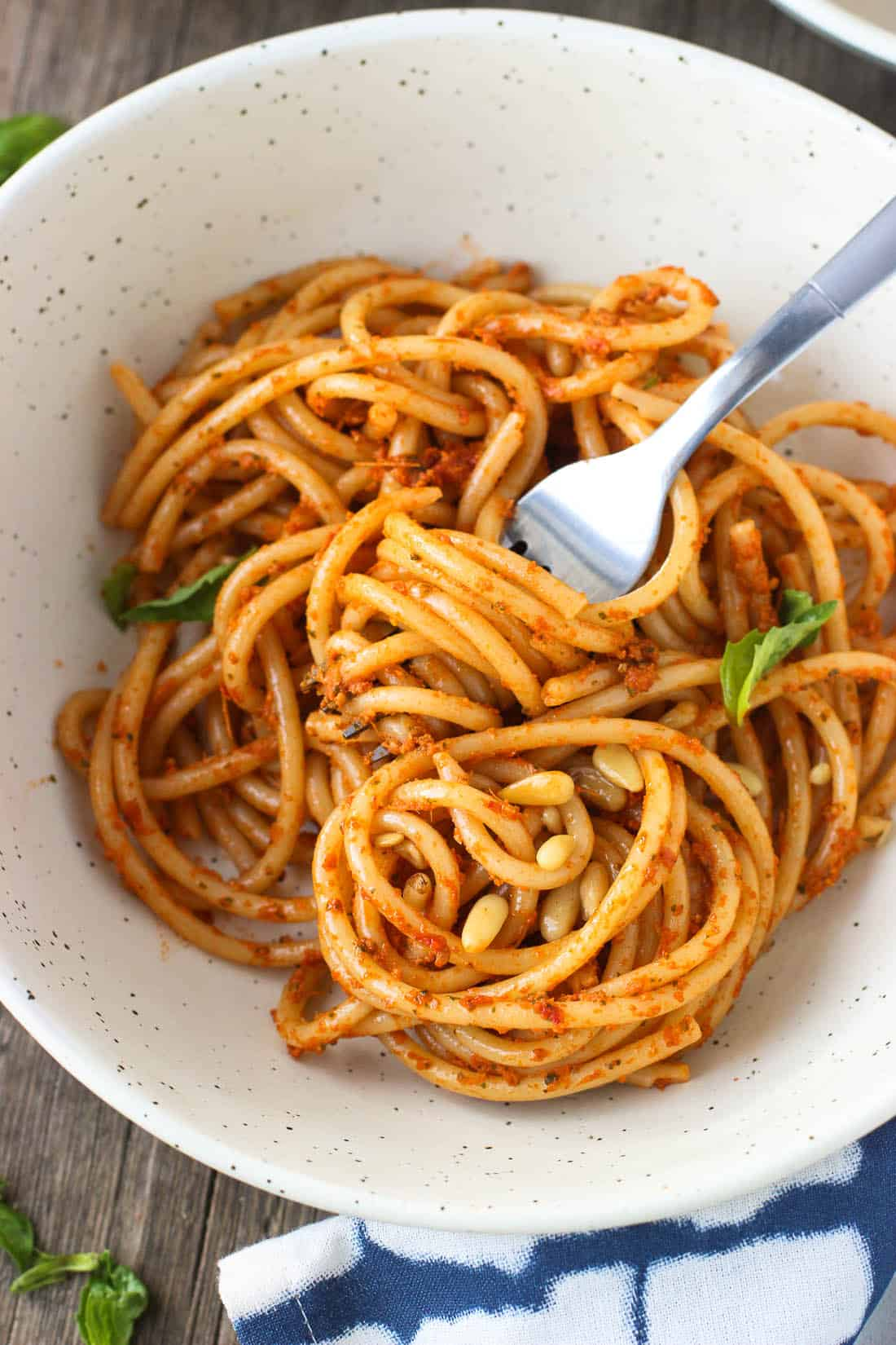 A dish of spaghetti coated with sun-dried tomato pesto garnished with basil leaves and pine nuts