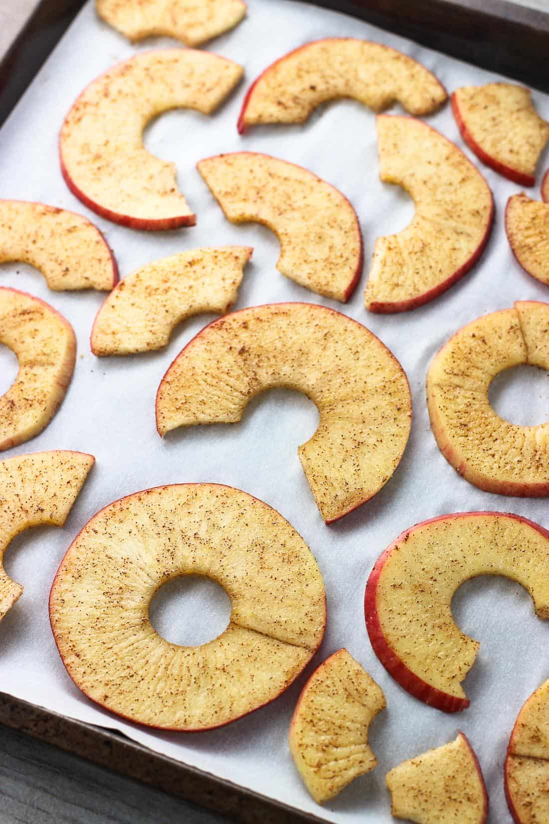 Raw spiralized apple rings sprinkled with cinnamon sugar on a parchment paper-lined rimmed metal baking sheet