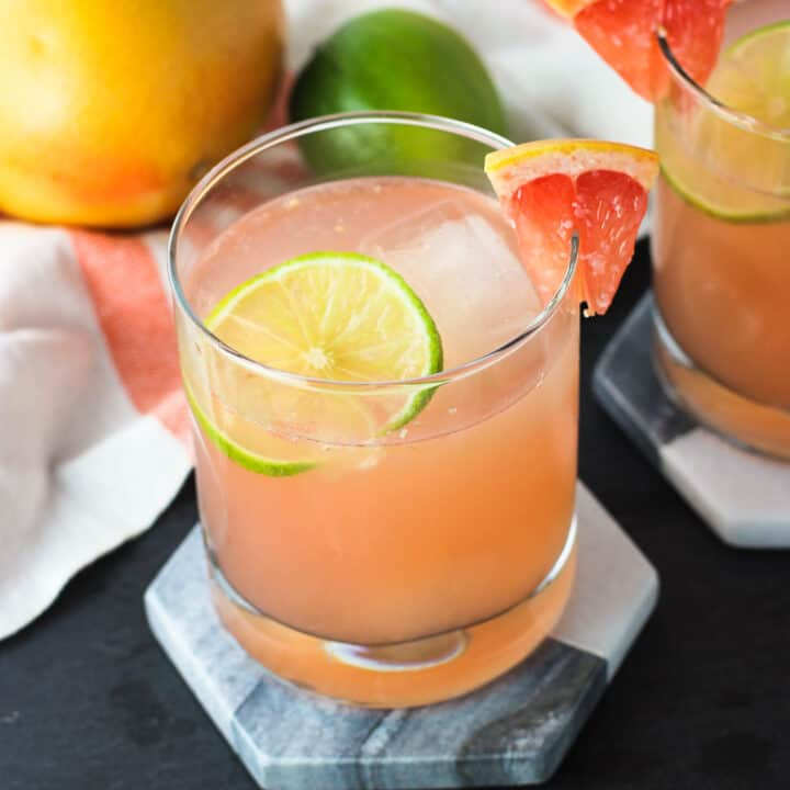 Two champagne palomas on marble coasters garnished with grapefruit wedges on the rims with lime rounds
