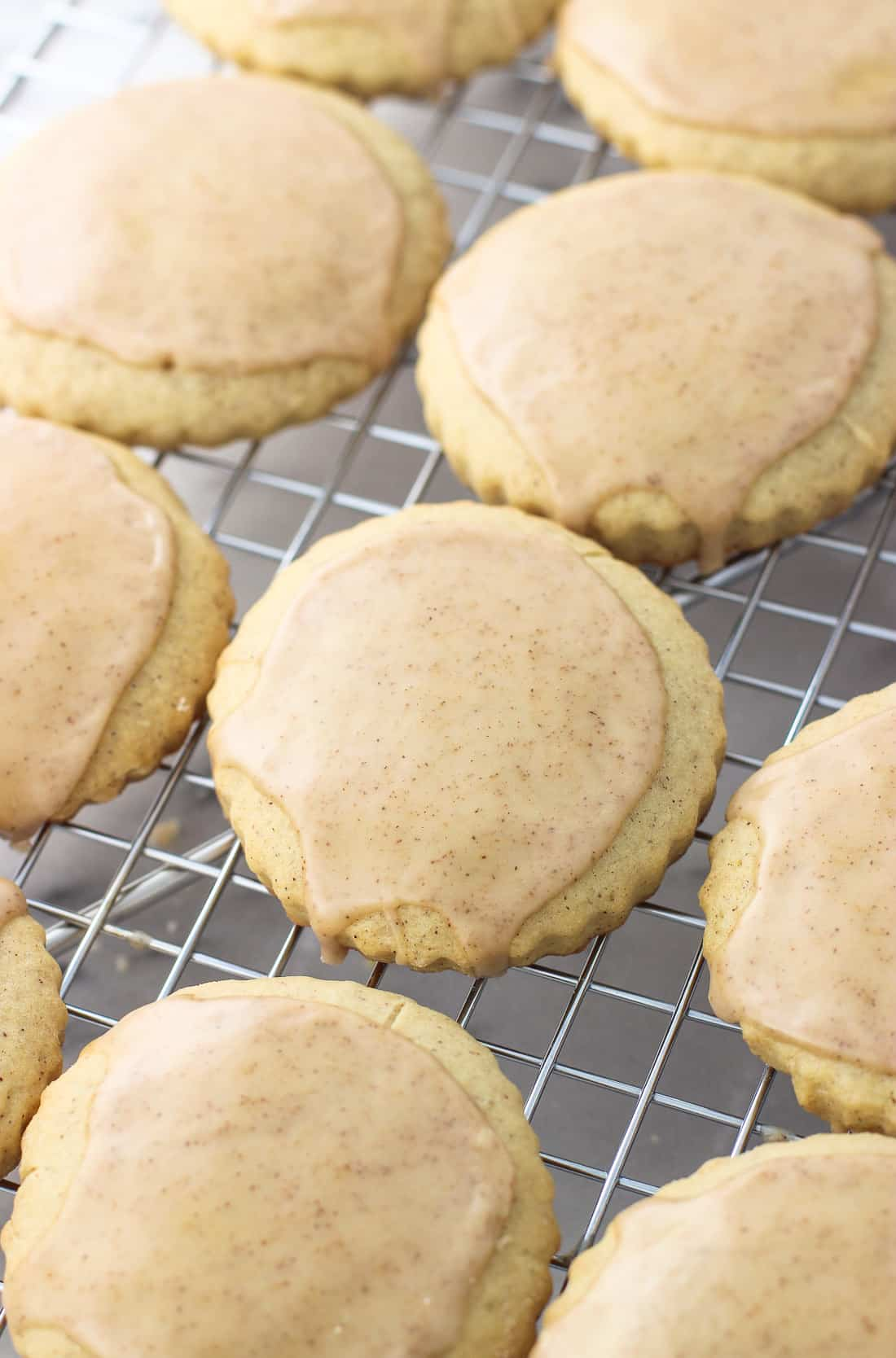 Iced cinnamon sugar cookies lined up on a wire rack.