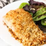 A fillet of coconut macadamia crusted salmon on a dinner plate next to a mixed greens salad