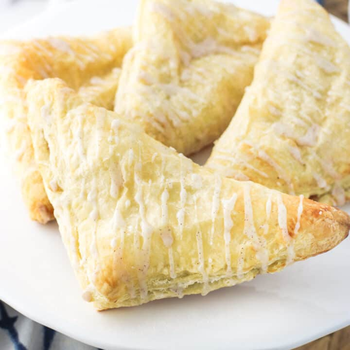 Easy puff pastry apple turnovers are bursting with apple pie flavor, with a filling that can be prepared a variety of different ways. A simple drizzle of glaze flavored with apple pie spice is all you need as a finishing touch on these flaky, fruit-filled pastries.