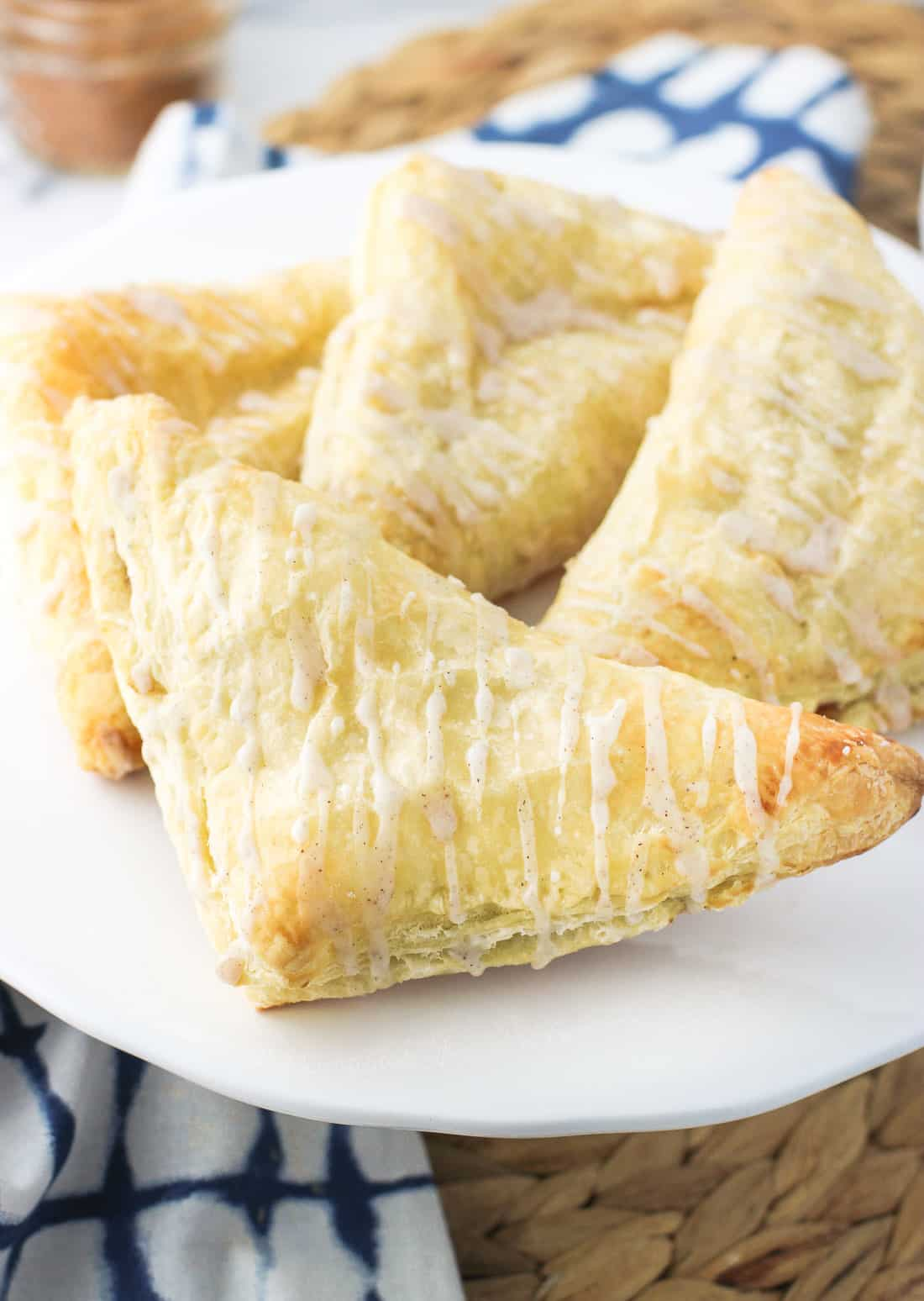 Four apple turnovers on a cake stand.