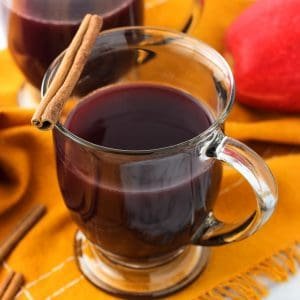 Two clear glass mugs of mulled wine garnished with cinnamon sticks