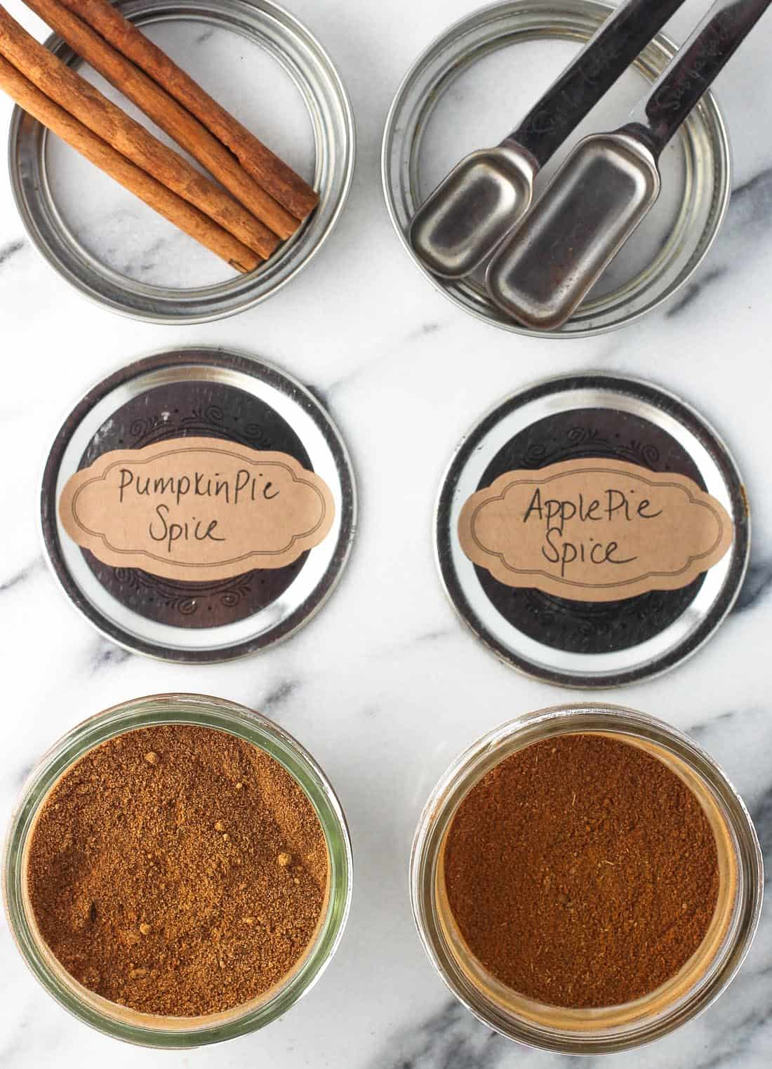 Jars and lids of pumpkin pie spice (left) and apple pie spice (right).