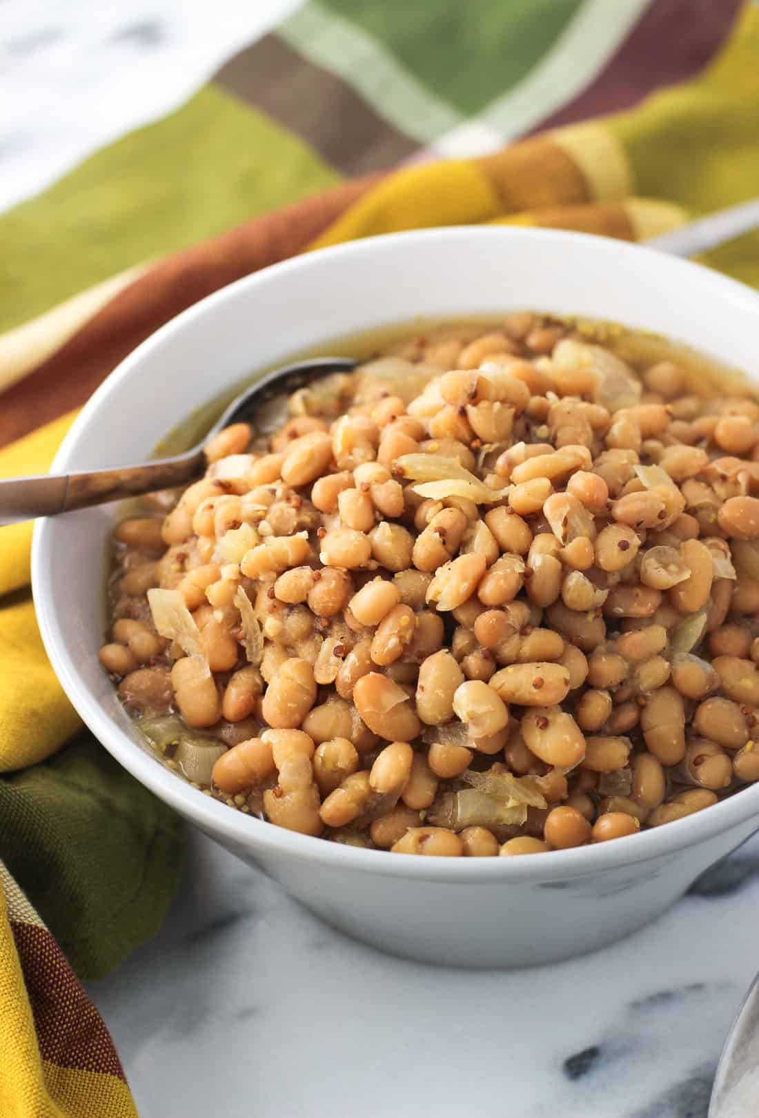 Slow cooker white beans are cooked in a whole grain mustard beer sauce for a flavorful and healthy side dish. This is a hearty crock pot recipe with easy prep!