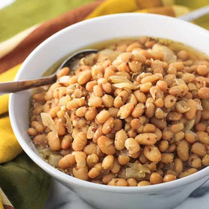 A bowl of white beans in a mustard beer sauce in a serving bowl with a spoon
