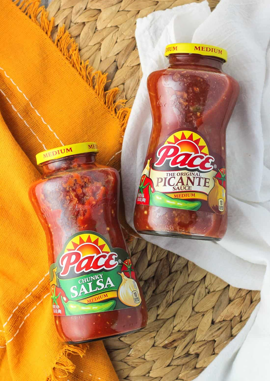 An overhead picture of two jars on a woven placemat - one Pace chunky salsa and the other Pace picante sauce