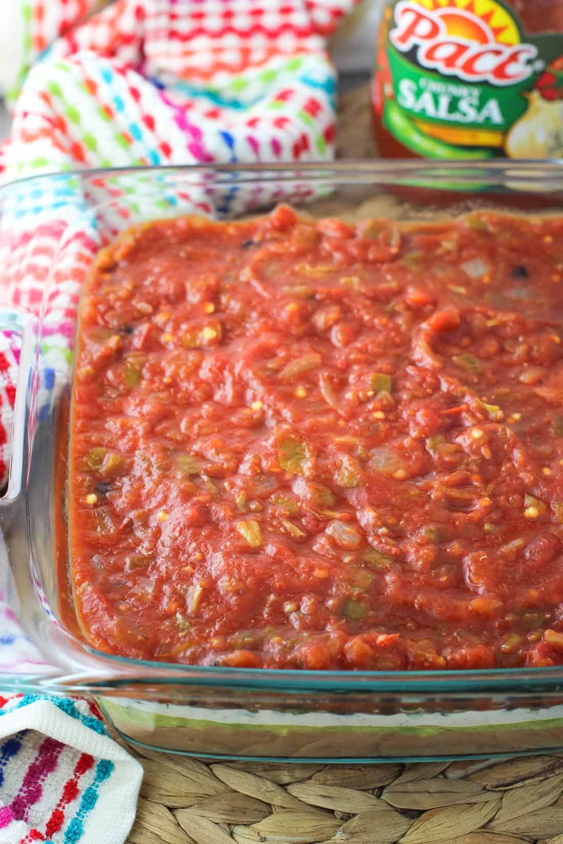 Seven layer dip in a glass baking dish, with the salsa layer on top