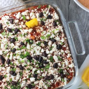 """An overhead picture of seven layer dip in a clear glass 8""""x8"""" dish next to a bowl of hot blended dip and a bowl of tortilla chips"""