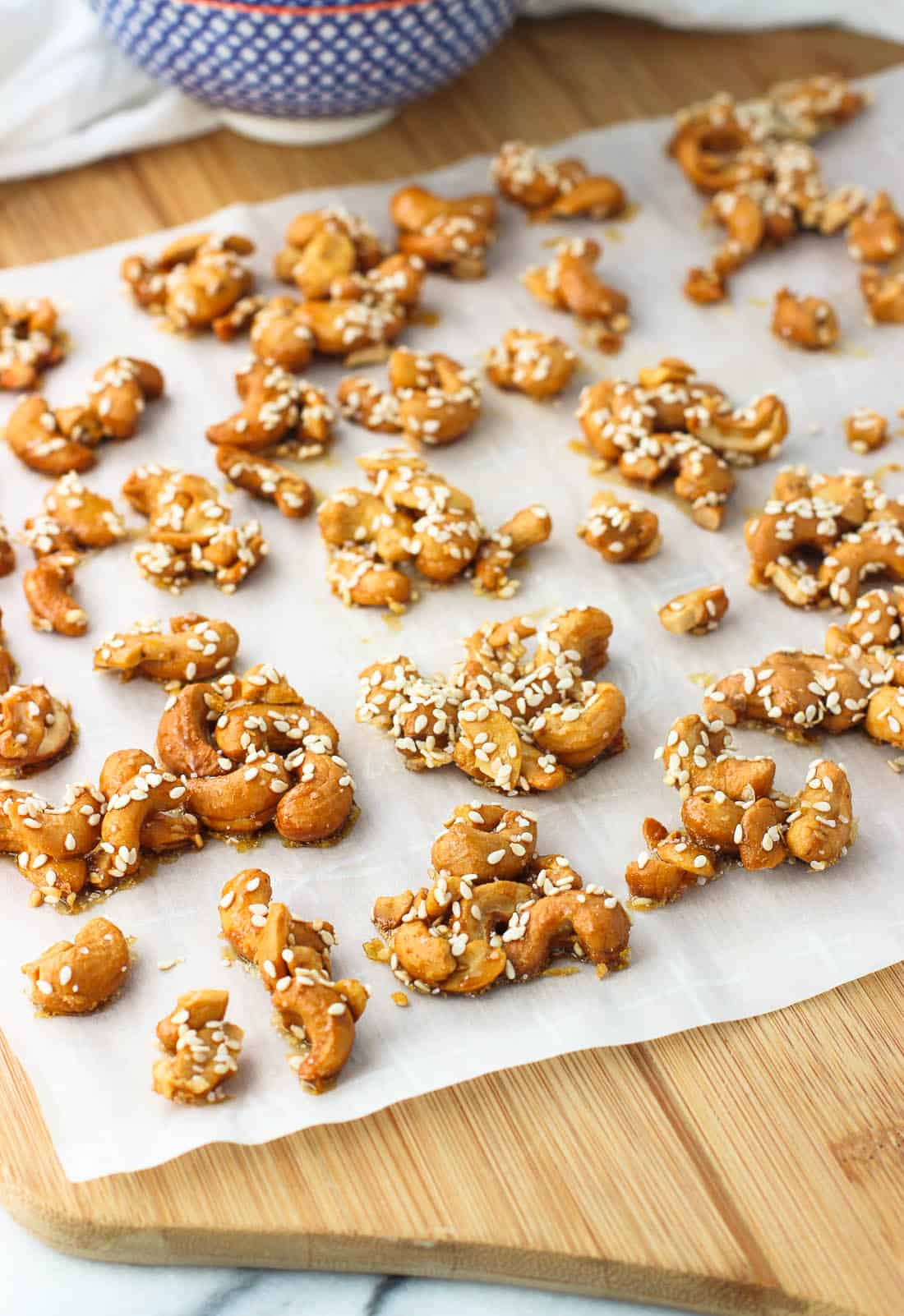 Cashew clusters on a sheet of parchment paper on a wooden board
