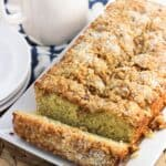 Sliced lemon poppy seed bread on a rectangular serving plate with a mug of tea in the background