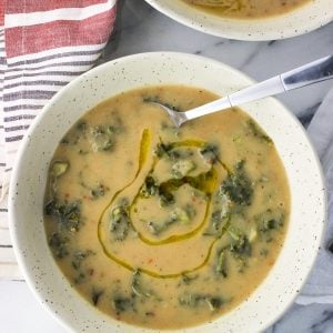 A bowl of soup with a spoon drizzled with an olive oil swirl.