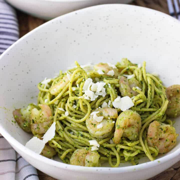 A bowl of spaghetti coated in pesto sauce topped with shrimp and shaved Parmesan cheese