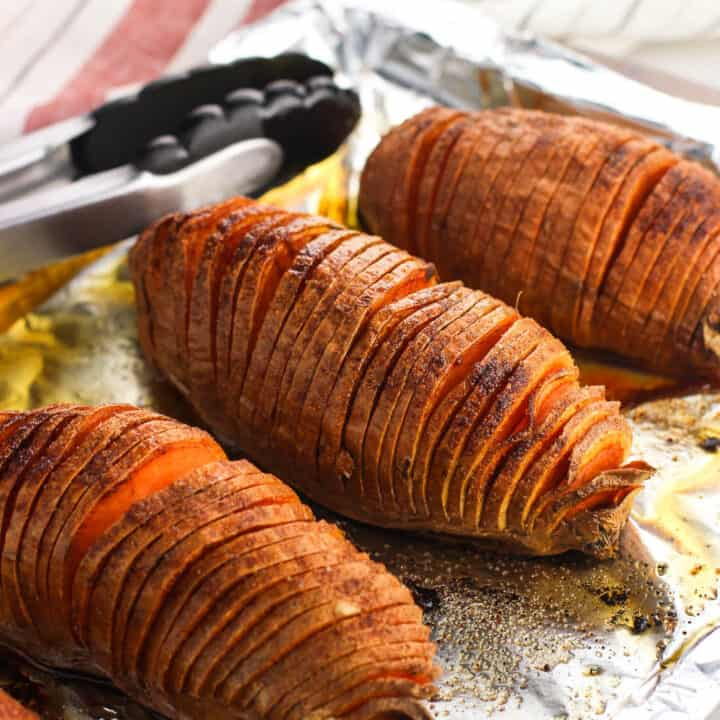Hasselback cut sweet potatoes on an aluminum foil-lined baking sheet with tongs in the background