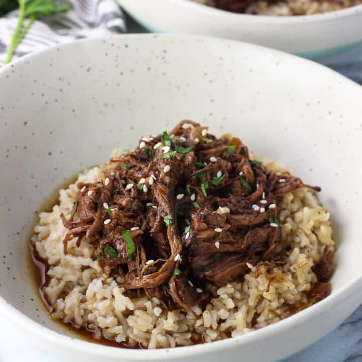 A pile of shredded beef served over brown rice in a shallow dinner bowl