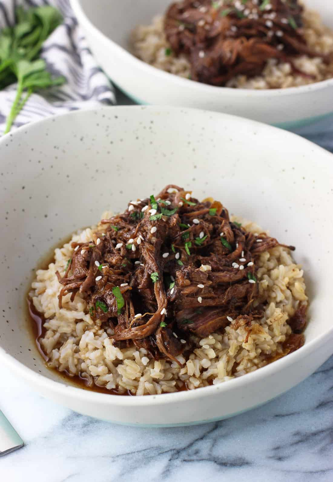 Slow cooker shredded beef is easy to make and versatile to use in sandwiches, over rice or salads, and more! It cooks in a balsamic peanut sauce that tastes amazing made in the crock pot.