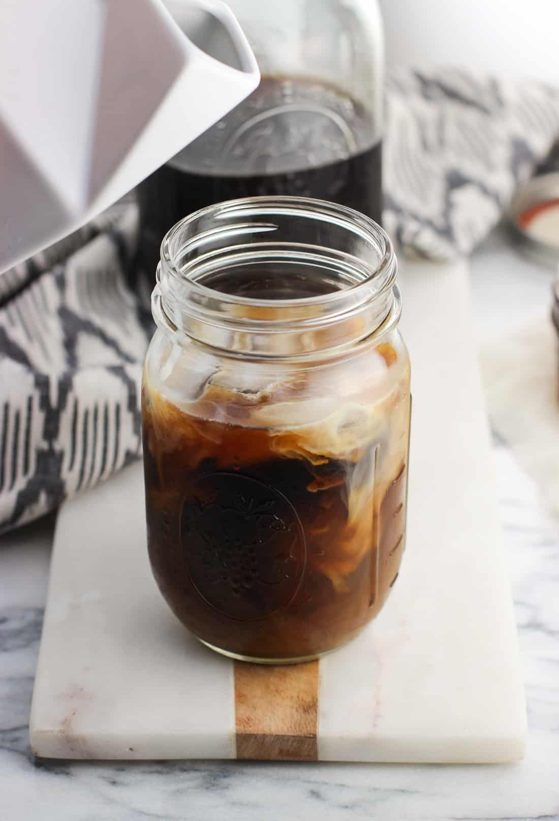 A ceramic milk carton hovering above a mason jar of coffee swirled with milk after pouring some in