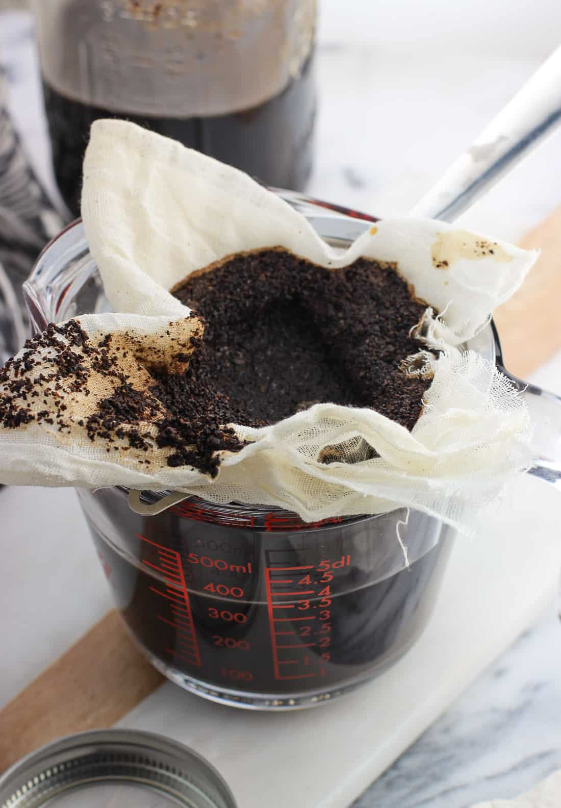 Wet coffee grounds in a cheesecloth-lined strainer set over a large glass measuring cup after the coffee has filtered through
