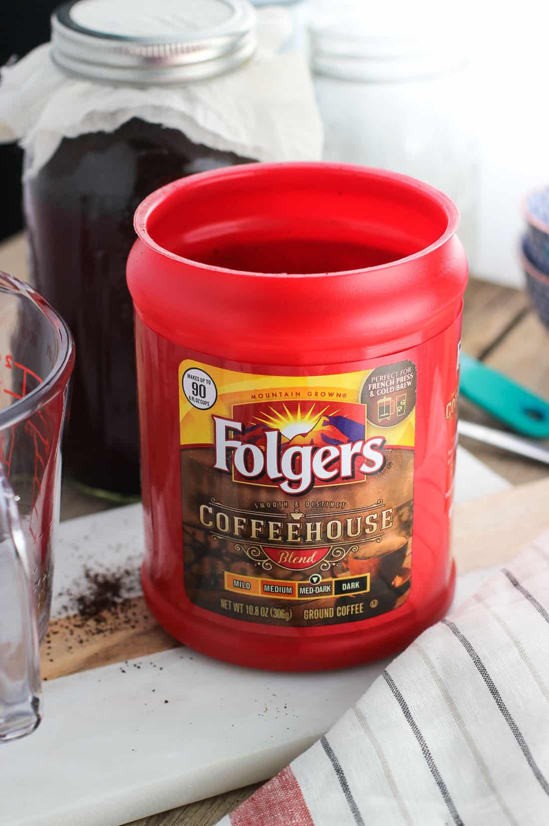 A plastic carton of Folgers Coffeehouse Blend ground coffee on a board in front of a jar of cold brew coffee