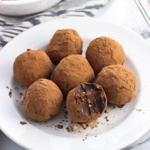 Peanut butter truffles on a small plate with a bite taken out of the front truffle.