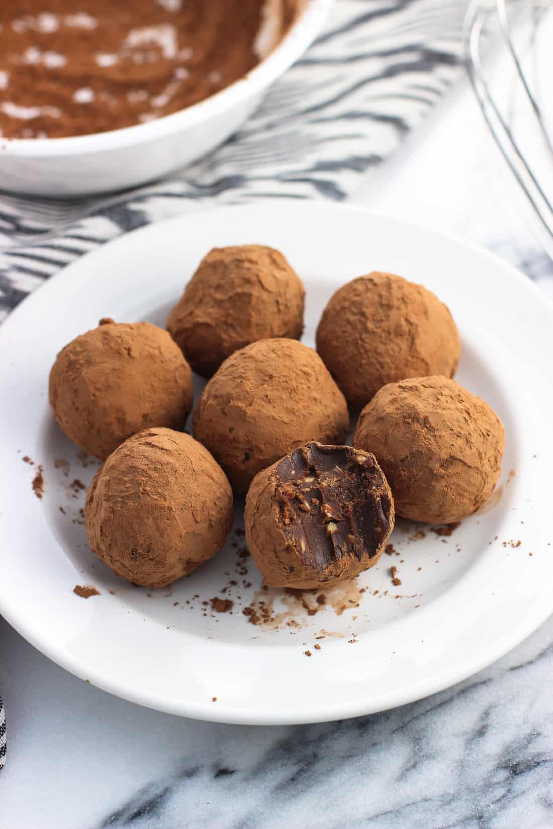 Seven truffles dusted in cocoa powder on a ceramic dessert plate, with the front truffle having a bite taken out of it. A bowl of cocoa powder and a whisk are in the background.