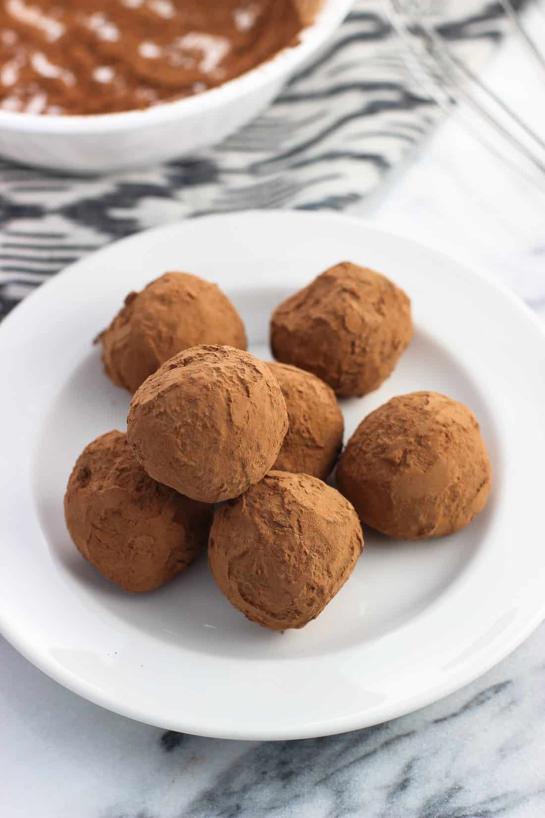 Seven truffles piled on a ceramic dessert plate with a bowl of cocoa powder and a whisk in the background