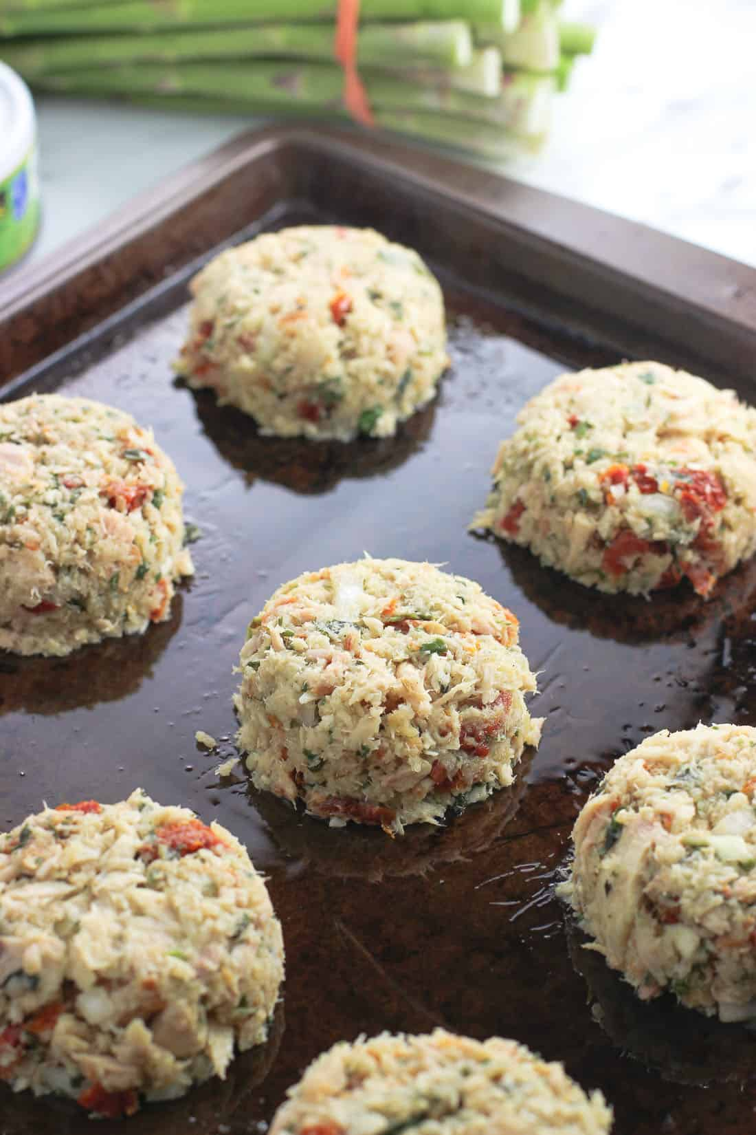 Formed tuna cake mixture on a sprayed metal baking sheet before being baked