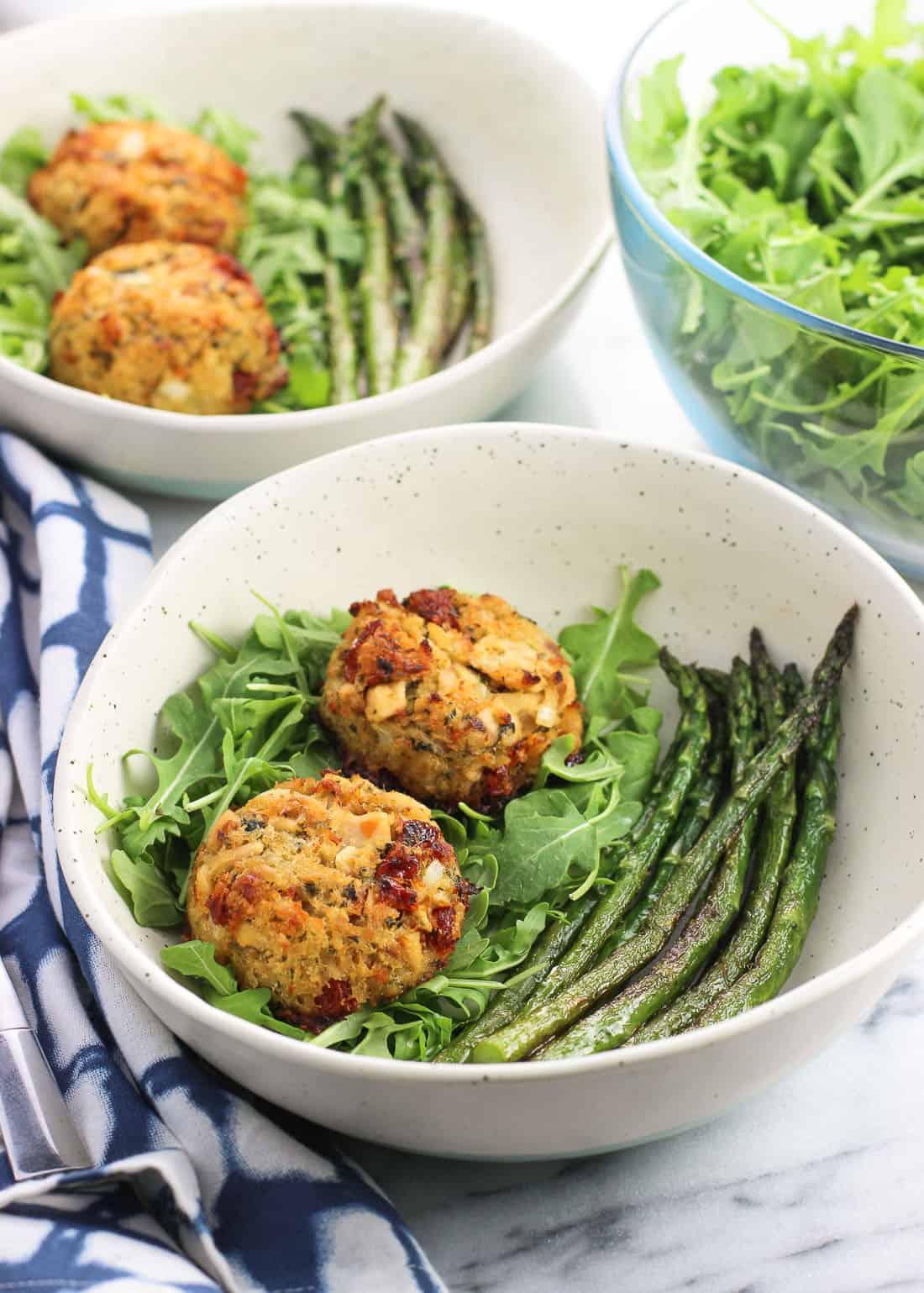 Two plates containing tuna cakes, arugula, and sauteed asparagus