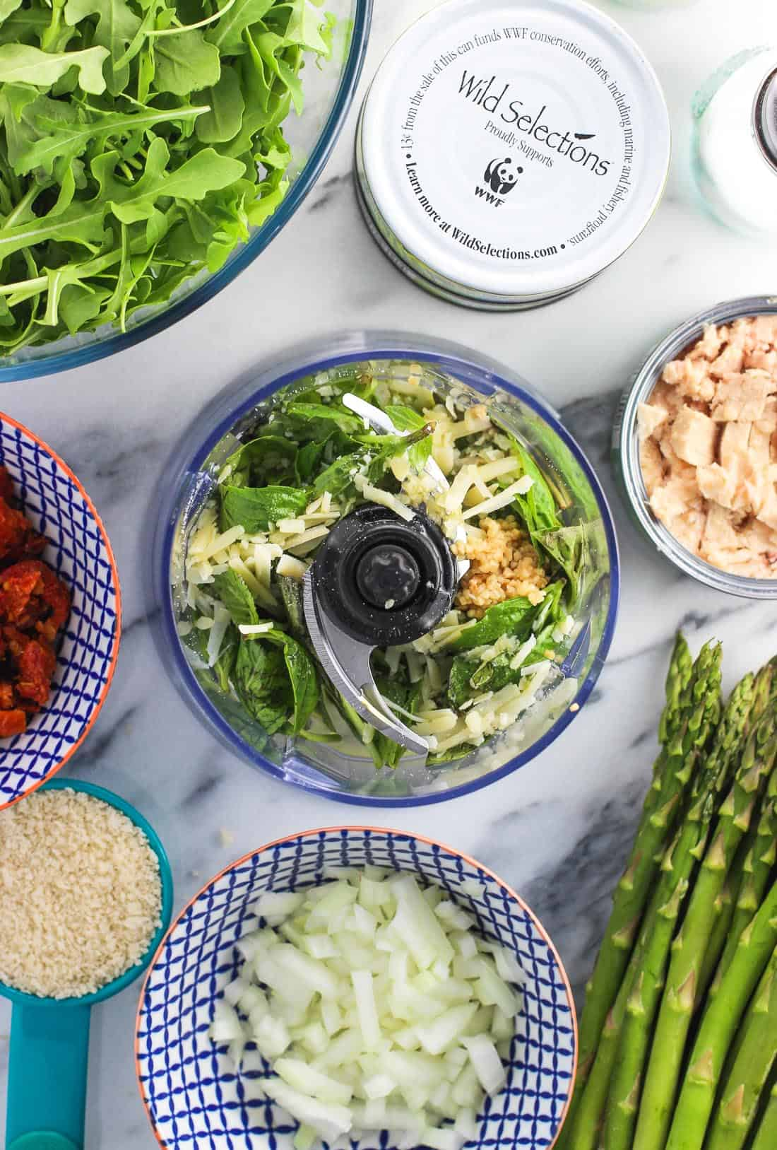 An overhead shot of ingredients in the food processor next to open cans of tuna, a bunch of asparagus, a bowl of arugula, etc.
