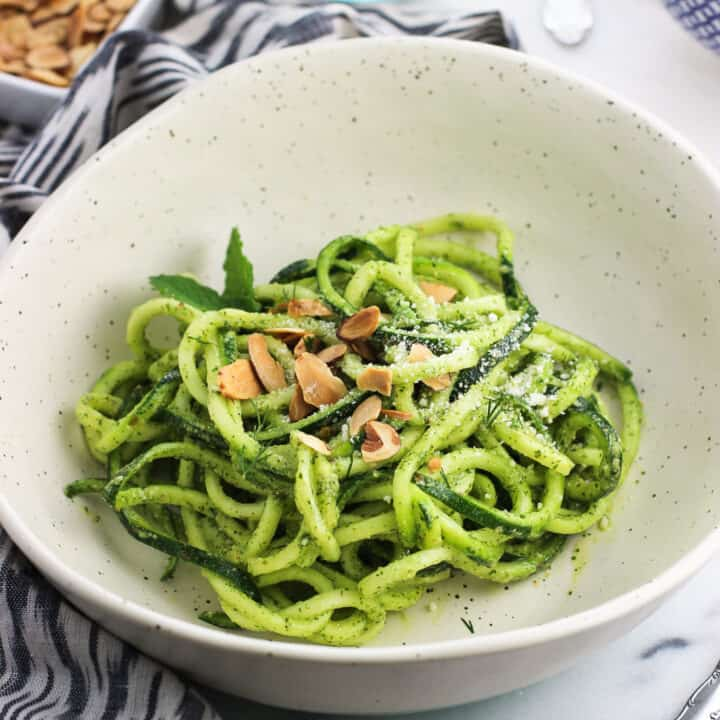 Zucchini noodles in a bowl covered in mint pesto sauce and garnished with toasted slivered almonds
