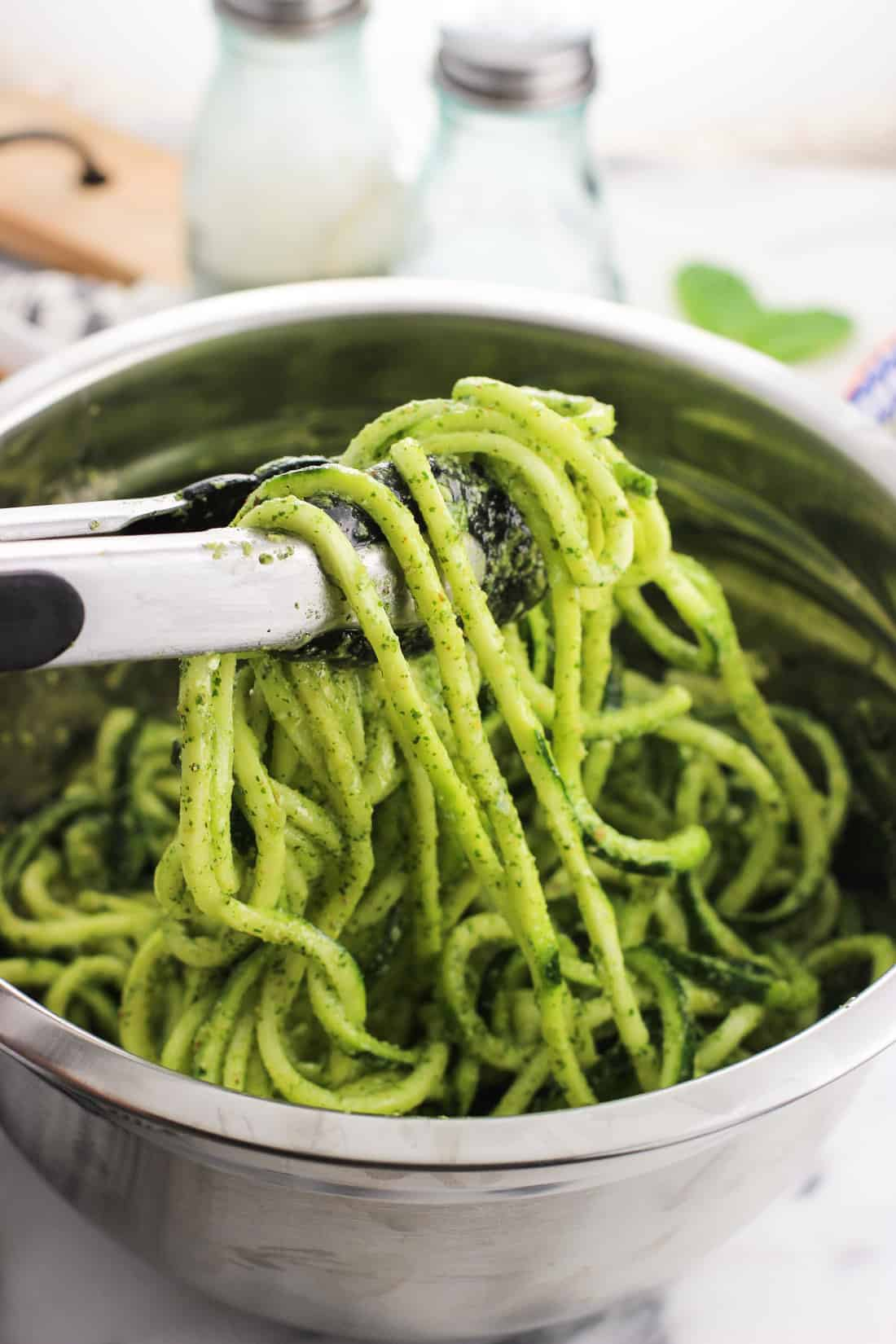 Tongs lifting up a section of zoodles dressed in pesto sauce from a medium metal bowl