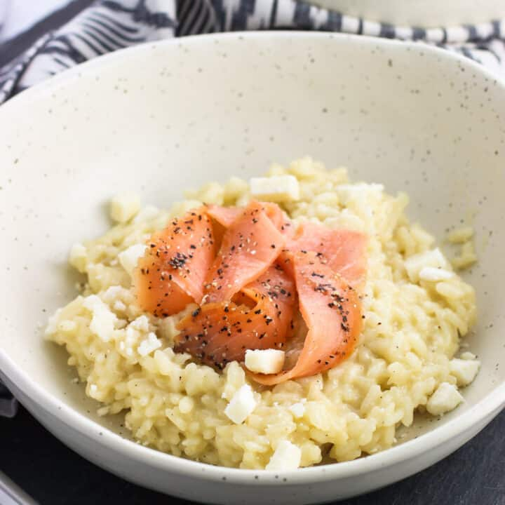 A shallow dinner bowl of risotto topped with smoked salmon slices and crumbled feta