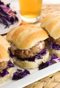 Juicy dill and ginger pork burgers are flavored with simple ingredients for a bold and balanced taste. These burgers can be grilled or baked on a rack in the oven for an all-weather meal. Serve with purple cabbage and two-ingredient creamy chili garlic sauce.